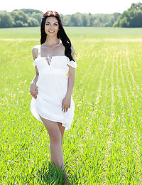 Watch this mind blowing brunette posing and getting fully naked while walking across a green farmland.